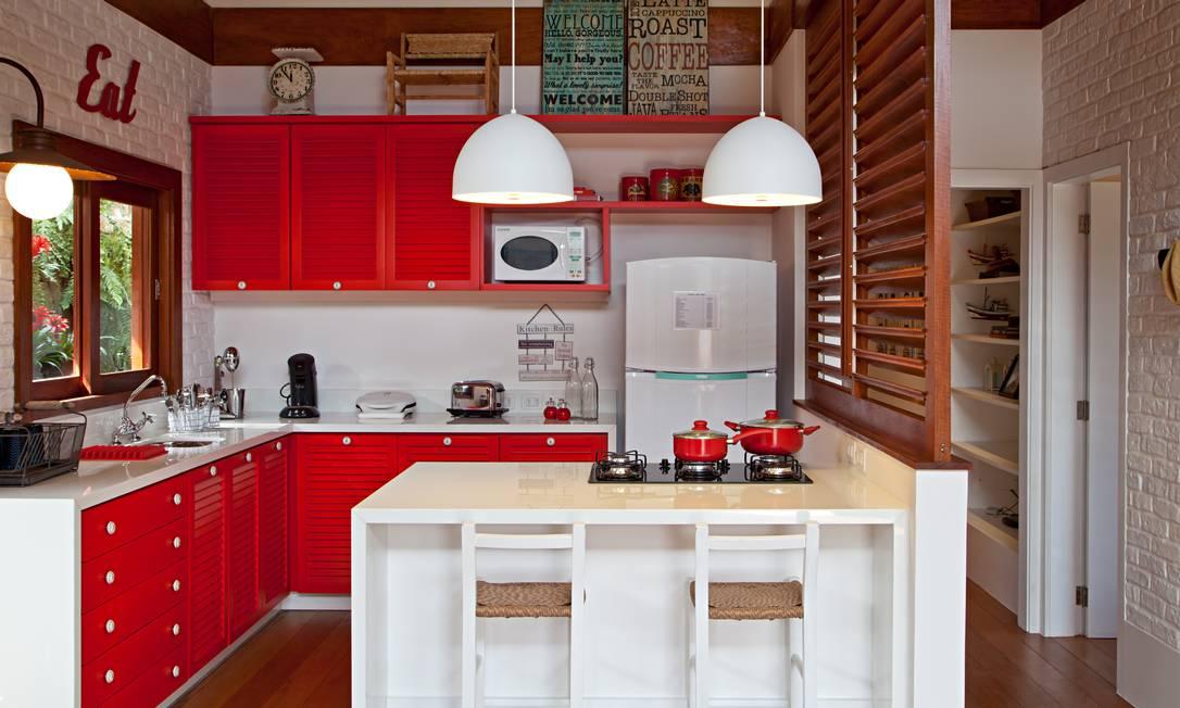 O vermelho nas portas de armários e gavetas aquece a cozinha projetada por Maurício Nóbrega Foto: Rodrigo Azevedo / Divulgação