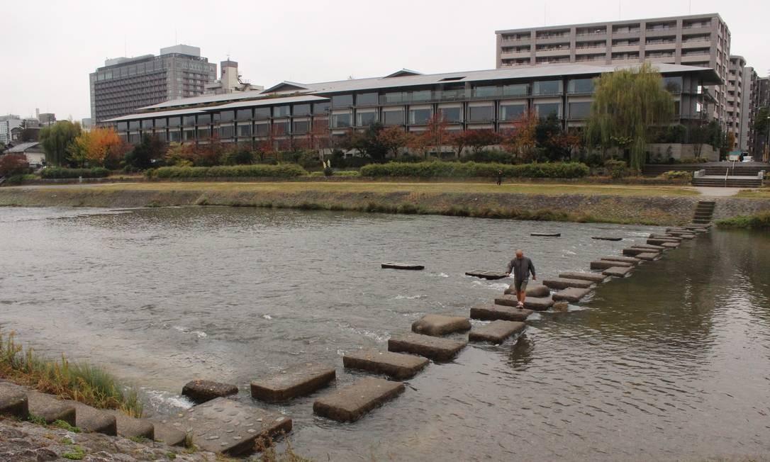 Homem atravessa o Rio Kamogawa depois de caminhada pela margem, atividade comum nesta área central de Kioto Foto: Léa Cristina / Agência O Globo