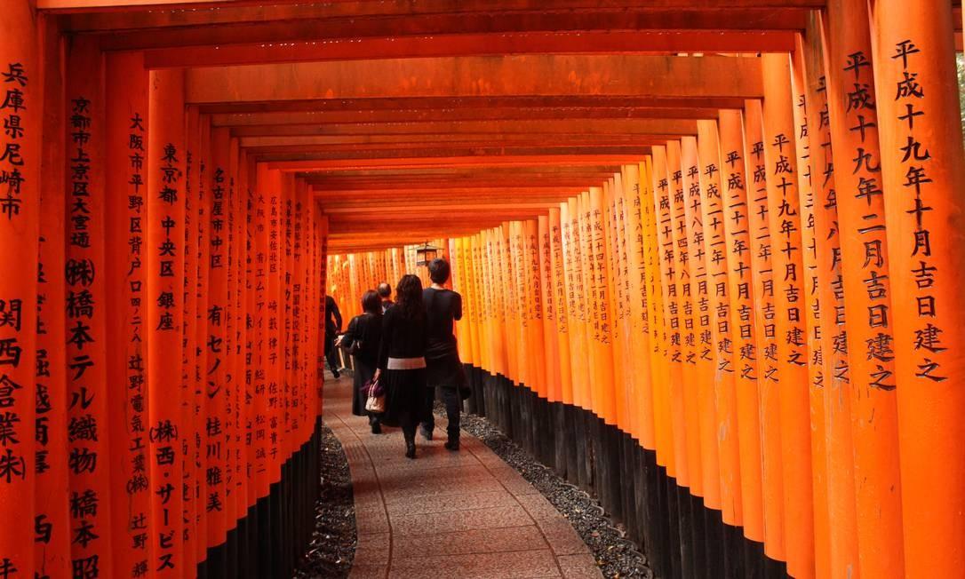Turistas andam pelo túnel de toriis (portais) no templo de Fushimi Inari, em Kioto Foto: Léa Cristina / Agência O Globo