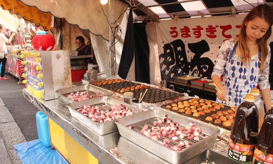 Na feirinha do Fushimi Inari, templo de Kioto, moça vende bolinhas de polvo (seis unidades a US$ 5) Foto: Léa Cristina / Agência O Globo