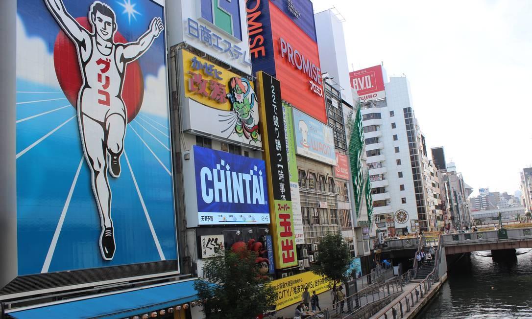 Glico Man, no cartaz à esquerda, personagem famoso da marca de biscoitos e doces Glico. Às margens do canal em Dotonbori, Osaka Foto: Léa Cristina / Agência O Globo