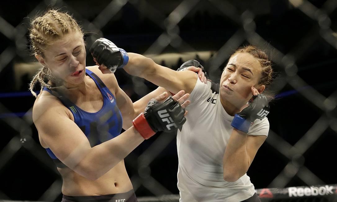 Michelle Waterson acerta um cruzado de direita em Paige VanZant antes de colocar a rival no chão e finalizá-la com estrangulamento no primeiro round Jeff Chiu / AP