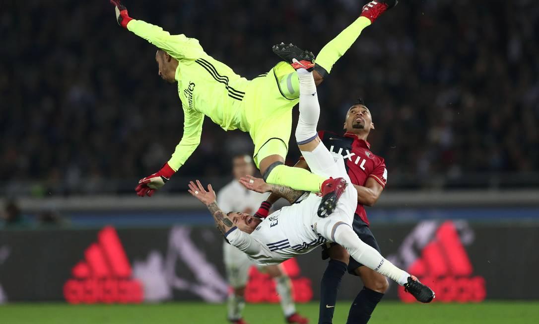 O goleiro do Real Madrid, Keylor Navas sai no alto, num salto acrobático, para impedir que a bola chegue ao brasileiro Fabrício no ataque do Kashima Antlers na final do Mundial de Clubes da Fifa BEHROUZ MEHRI / AFP