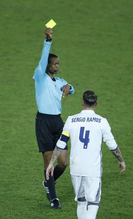 O árbitro Janny Sikazwe dá cartão amarelo para o capitão do Real Madrid, Sérgio Ramos. Mas no fim do tempo normal o juiz evitou punir novamente o zagueiro, que tinha feito falta para amarelo e seria expulso se recebesse o segundo Foto: Reuters / Issei Kato / REUTERS
