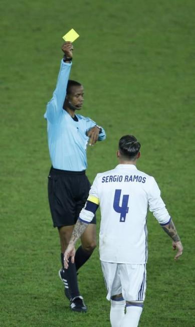 O árbitro Janny Sikazwe dá cartão amarelo para o capitão do Real Madrid, Sérgio Ramos. Mas no fim do tempo normal o juiz evitou punir novamente o zagueiro, que tinha feito falta para amarelo e seria expulso se recebesse o segundo Reuters / Issei Kato / REUTERS
