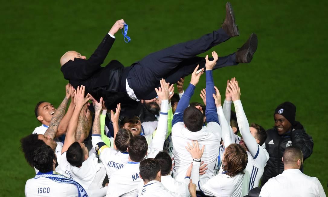 Jogadores do Real Madrid jogam para o alto o técnico Zinedine Zidane: em 2016 o time conquistou a Liga dos Campeões da Europa e o Mundial de Clubes, no Japão TORU YAMANAKA / AFP