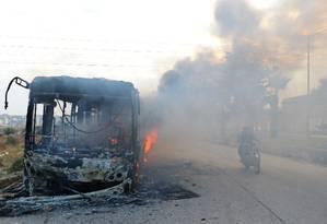 Um dos ônibus incendiados ainda queimando na estrada para as vilas xiitas de al-Foua e Kefraya: ataque coloca em risco reinício da evacuação de milhares de civis e combatentes rebeldes do Leste de Aleppo Foto: REUTERS/AMMAR ABDULLAH