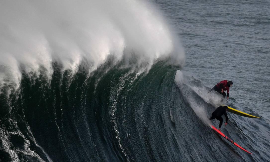 O surfista peruano Gabriel Villaran (acima) e o português Nicolau Von Krup, dividindo a mesma onda FRANCISCO LEONG / AFP