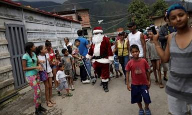 Festa na penúria. Papai Noel visita favela em Caracas: inflação de três dígitos e falta de recursos para presentes Foto: UESLEI MARCELINO / REUTERS/11-12-2016