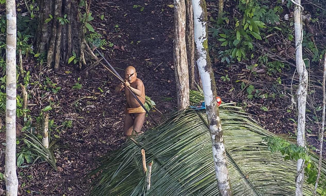 Índio empunha arco e flecha durante sobrevoo de aeronave sobre a tribo isolada no Acre Foto: Ricardo Stuckert / Agência O Globo