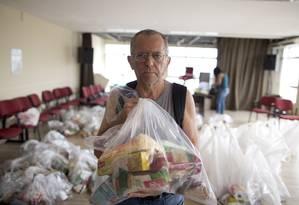 Servidor segura cesta básica que recebeu de doação Foto: Márcia Foletto / O Globo