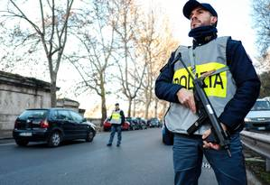 Policiais seguram armas em posto de controle no centro de Roma na véspera de Natal Foto: ANDREAS SOLARO / AFP
