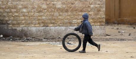 Criança brinca com um pneu dentro de uma escola danificada na aldeia de Tal-Aar, na província de Aleppo, na Síria Foto: KHALIL ASHAWI / REUTERS