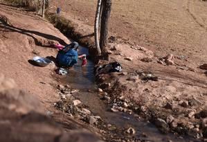 Nesta fotografia tirada em 5 de novembro de 2016, uma mulher afegã lava roupas em um canal no distrito Yakawlang da província de Bamiyan Foto: WAKIL KOHSAR / AFP