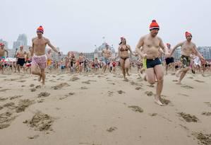 Pessoas correm em direção às geladas águas do Mar do Norte para cumprir uma tradição de Ano Novo Foto: BART MAAT / AFP