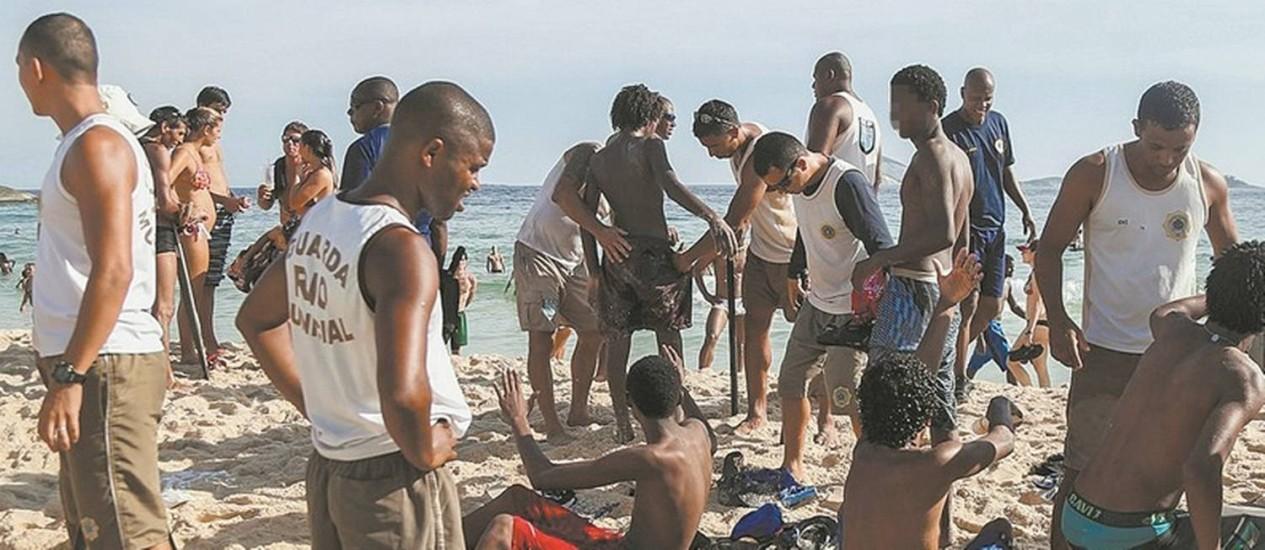 Na praia. Guardas municipais revistam menores após arrastão no Arpoador: hoje somente uso de cassetete é liberado Foto: Bárbara Lopes