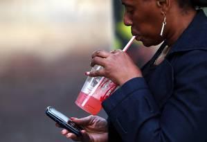 Mulher toma bebida em Nova York, em meio a discussões sobre uma proibição na cidade à venda de açucarados em grandes embalagens Foto: SPENCER PLATT / AFP
