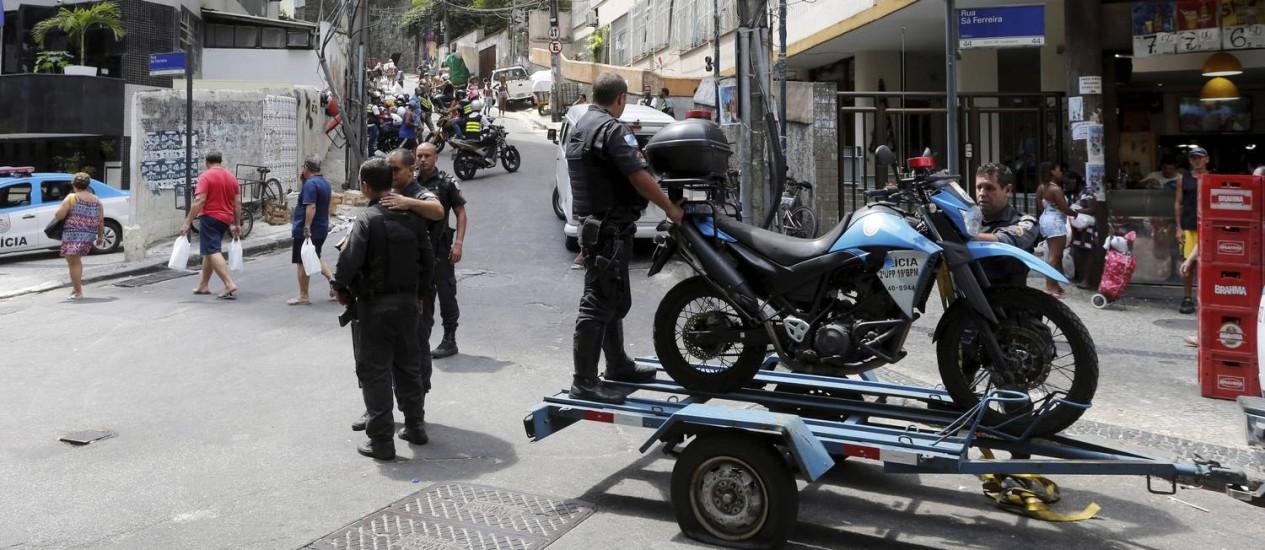 Policiais da UPP Pavão-Pavãozinho recolhem motocicleta atingida a tiros Foto: Domingos Peixoto / O Globo