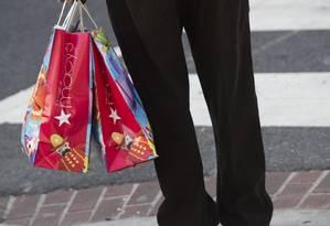 Consumidor carrega sacolas da Macy's, que anunciou demissão de dez mil funcionários e fechamento de 68 lojas. Foto: Saul Loeb/AFP