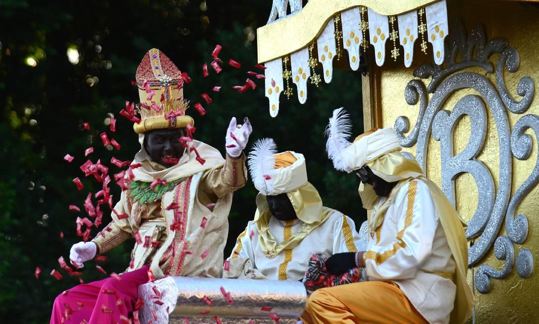 Um homem representando Baltasar, um dos Três Reis Magos, joga doces durante o desfile em Sevilha CRISTINA QUICLER / AFP
