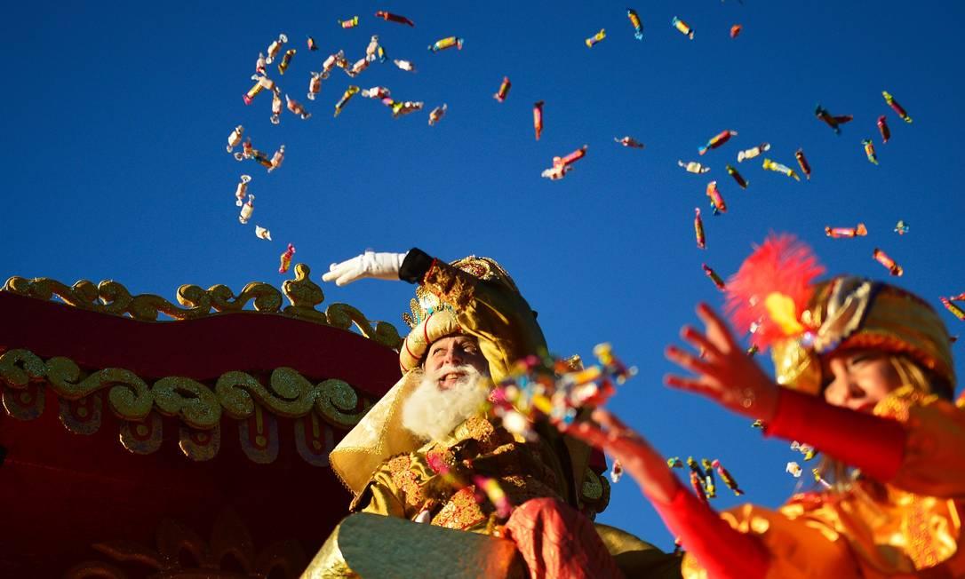 Um homem vestido como rei Gaspar, joga balas para o público, em Sevillha CRISTINA QUICLER / AFP