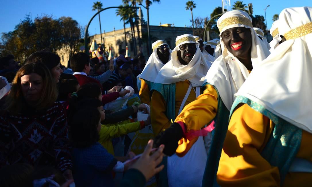 Participantes vestidos como beduinos servem doces para as crianças CRISTINA QUICLER / AFP