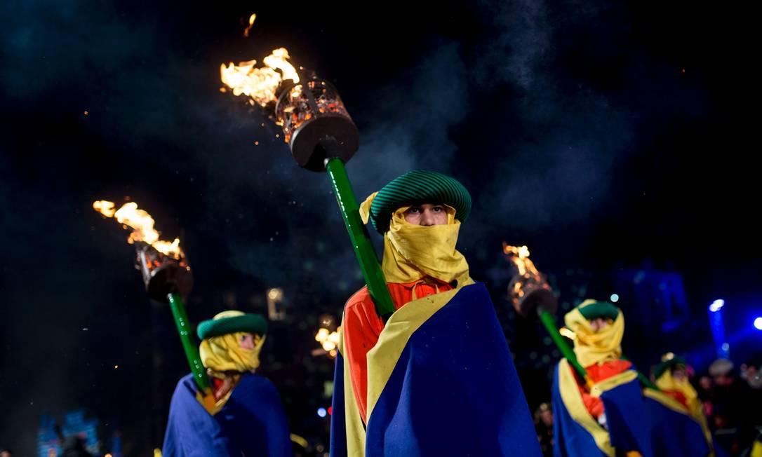 Participantes do desfile carregam tochas, marcando a véspera da festa da Epifânia JOSEP LAGO / AFP