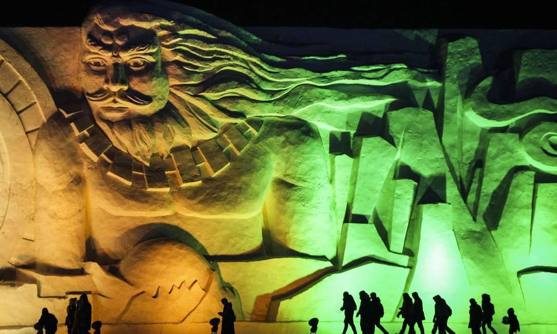 Visitantes passam por escultura gigante e iluminada durante a noite, em Harbin, na China AP