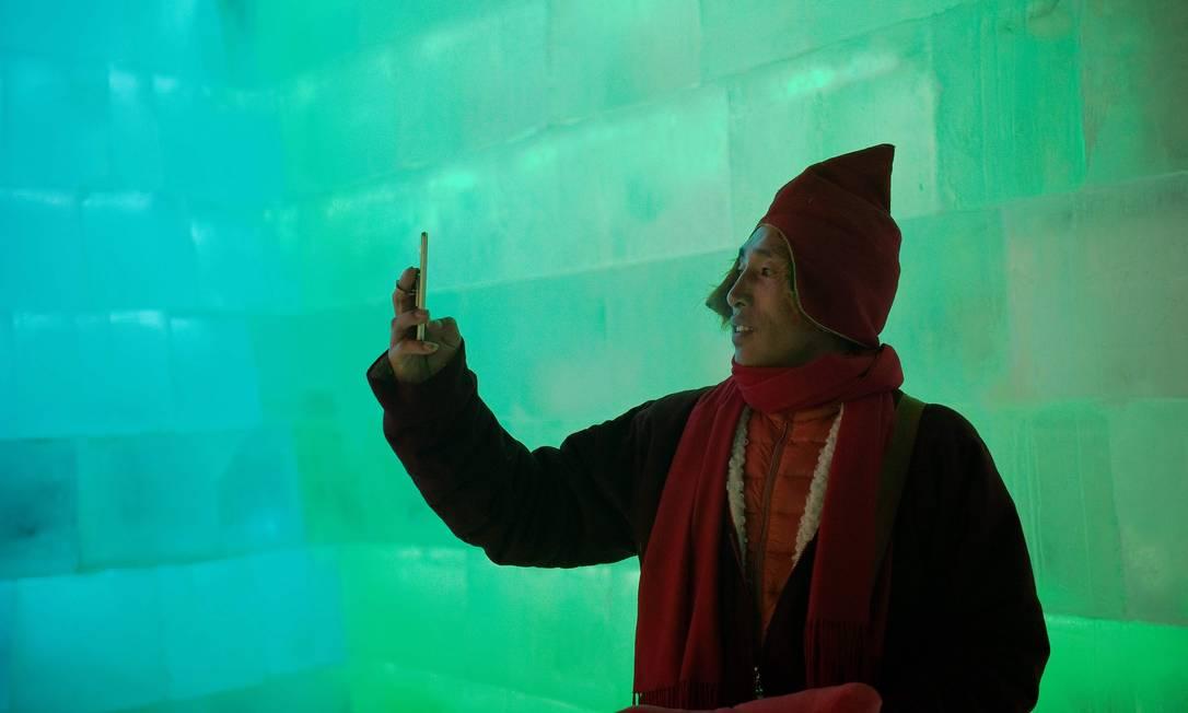 Um monge budista tibetano tira uma selfie enquanto visita o festival NICOLAS ASFOURI / AFP