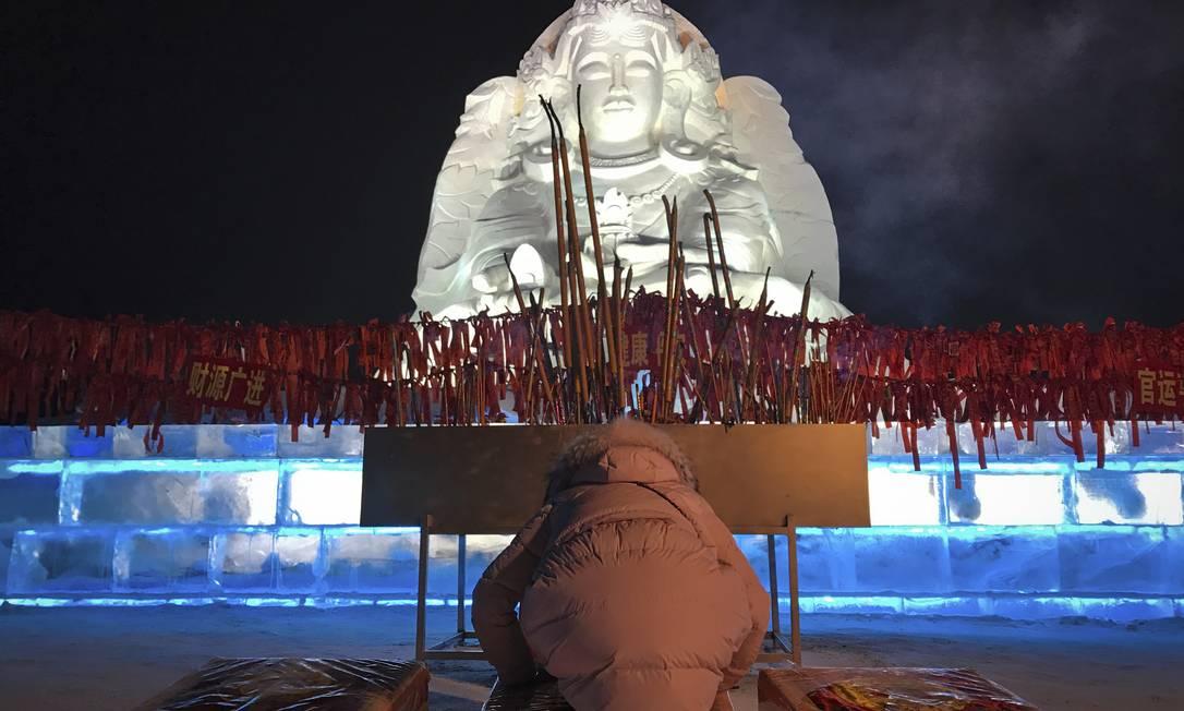 Chinesa reza em frente a uma escultura de gelo no Festival de Harbin Helene Franchineau / AP