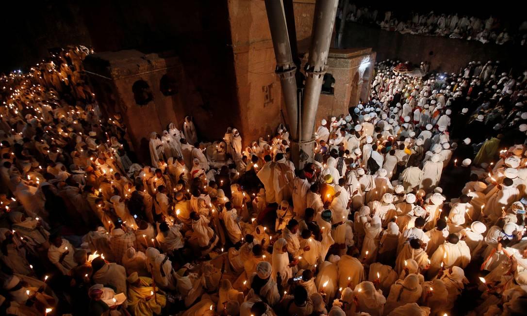 Fiéis seguram velas para a vigília de Natal ao redor da Igreja Casa de Maria, em Lalibela, na Etiópia TIKSA NEGERI / REUTERS