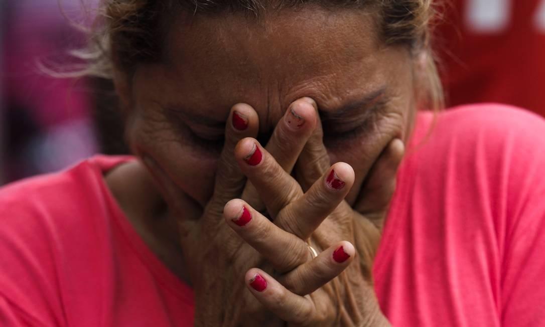 Mulher chora aliviada após saber que seu parente não está entre os mortos Foto: RAPHAEL ALVES / AFP