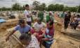 Parentes passam mal e se desesperam em enterro de presos que foram mortos durante a rebelião na Penitenciária Agrícola de Monte Cristo, em Roraima