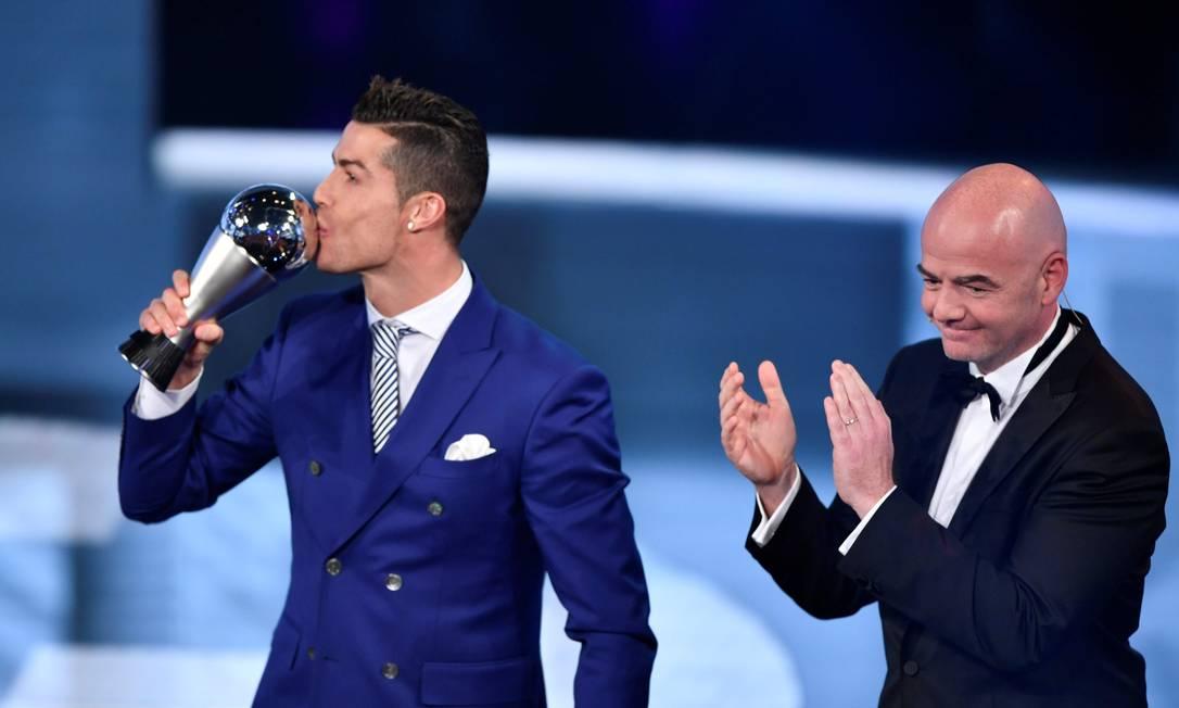 Aplaudido por Gianni Infantino, presidente da Fifa, Cristiano Ronaldo beija seu novo troféu de melhor do mundo FABRICE COFFRINI / AFP
