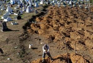 Homem abre covas no cemitério Tarumã, em Manaus, após a morte de 56 detentos durante rebelião Foto: UESLEI MARCELINO / REUTERS