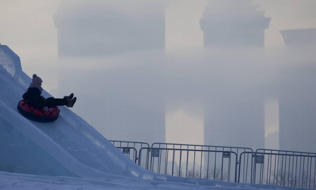 Mulher usa boia para deslizar em Moscou com temperatura de -21 Celsius Ivan Sekretarev / AP