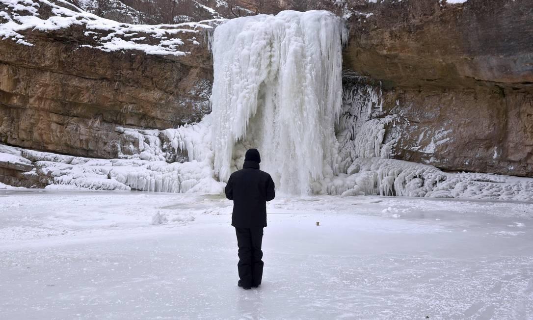 Em Kosovo homem observa uma cachoeira congelada ARMEND NIMANI / AFP