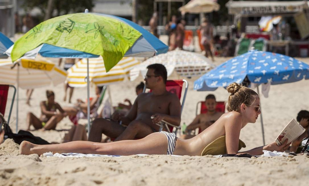 Jovem aproveita o sol para ler e tirar a marca do biquini Hermes de Paula / Agencia O Glob / Agência O Globo