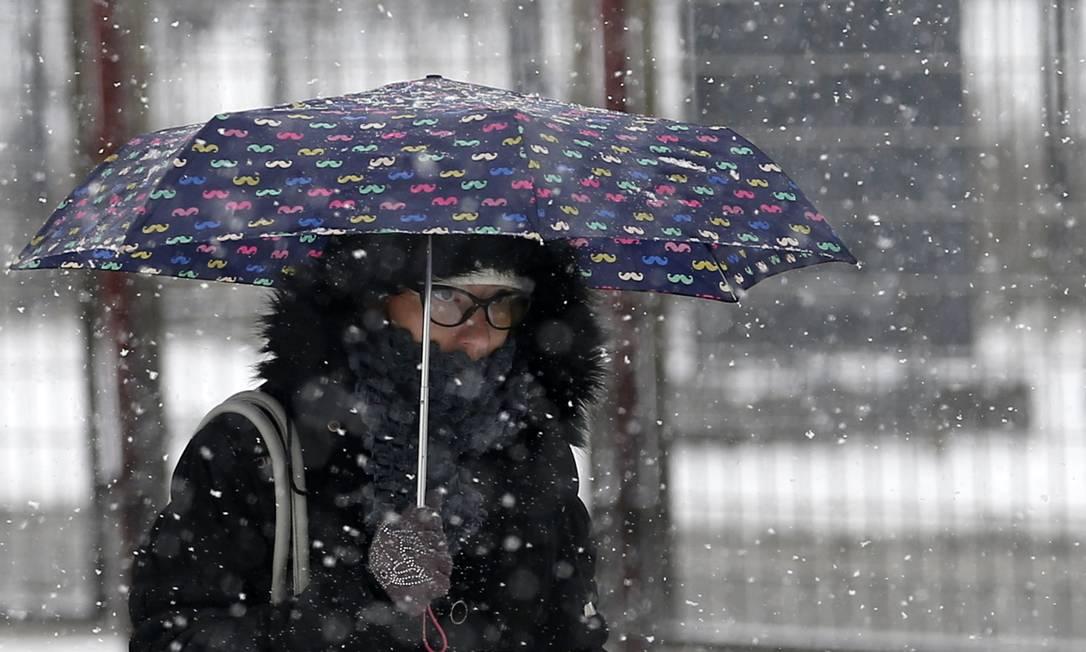 Mulher se protege da neve em Belgrado, na Sérvia com a temperatura caindo a -30º Celsius Darko Vojinovic / AP