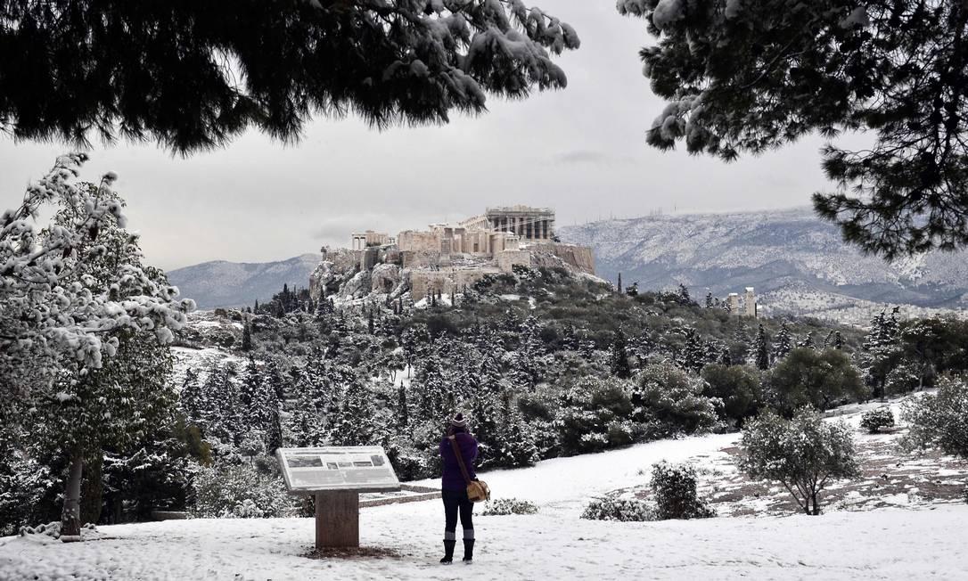 Mulher fotografa Acropolis, em Atenas. Mais de 30 pessoas morreram com o frio nos ultimos dias LOUISA GOULIAMAKI / AFP