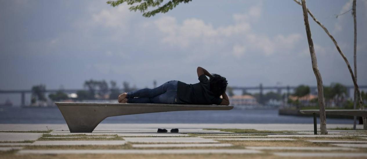 Mulher aproveita a pequena sombra nas imediações do Museu do Amanhã Foto: Márcia Foletto / Agência O Globo