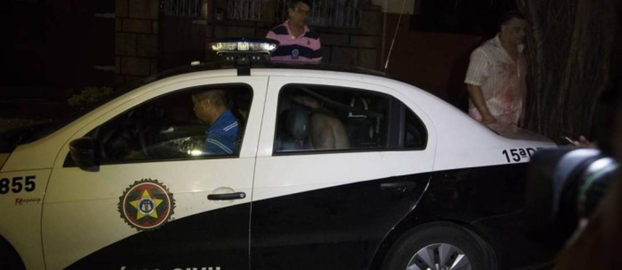 Noite do crime: policial que atirou contra a irmã está no interior da viatura; o irmão está do lado de fora com a camisa ensanguentada Foto: Agência O Globo