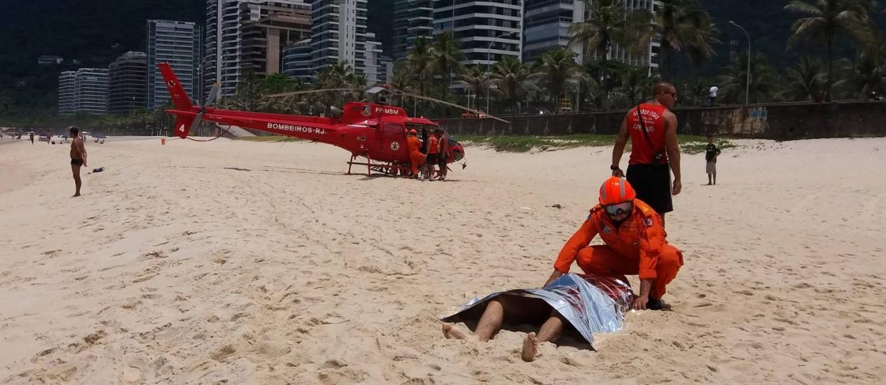 Bombeiro cobre um dos corpos achado na água por surfistas Foto: Custódio Coimbra / Agência O Globo