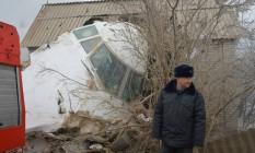 Policial trabalha ao lado de avião que colidiu contra casas no Quirguistão Foto: VYACHESLAV OSELEDKO / AFP