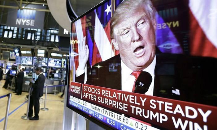 Trump é destaque nas TVs da Bolsa de Valores de Nova York Foto: Richard Drew / AP