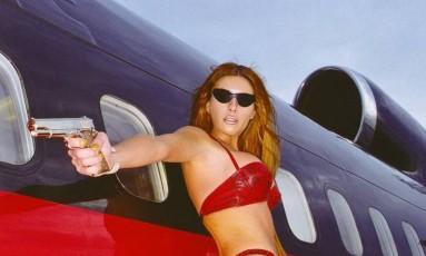 """Melania Trump ainda nem sonhava em ser primeira-dama dos Estados Unidos quando emprestava seu rosto e corpo para ensaios de moda. Dona de formas esculturais, a modelo eslovena ficou famosa por ensaios sensuais (e muitas vezes controversos - pense nessa arma da foto) que relembramos nessa galeria. Aqui, ela posa para a """"GQ"""" em 2000 Foto: Divulgação /"""