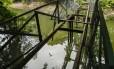 Assoalho da ponte do Canal das Taxas foi removido e é possível ver os jacarés junto ao esgoto Foto: Bárbara Lopes / Agência O Globo
