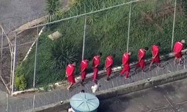 Presos do presídio Antônio Dutra Ladeira são levados de volta às suas celas, após motim Foto: Reprodução/TV Globo