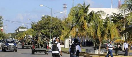 Policiais correm perto do prédio da promotoria em Cancún, no México Foto: AP