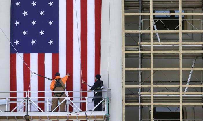 Funcionários instalam uma bandeira dos EUA na parte externa do Capitólio, em Washington Foto: Patrick Semansky / AP